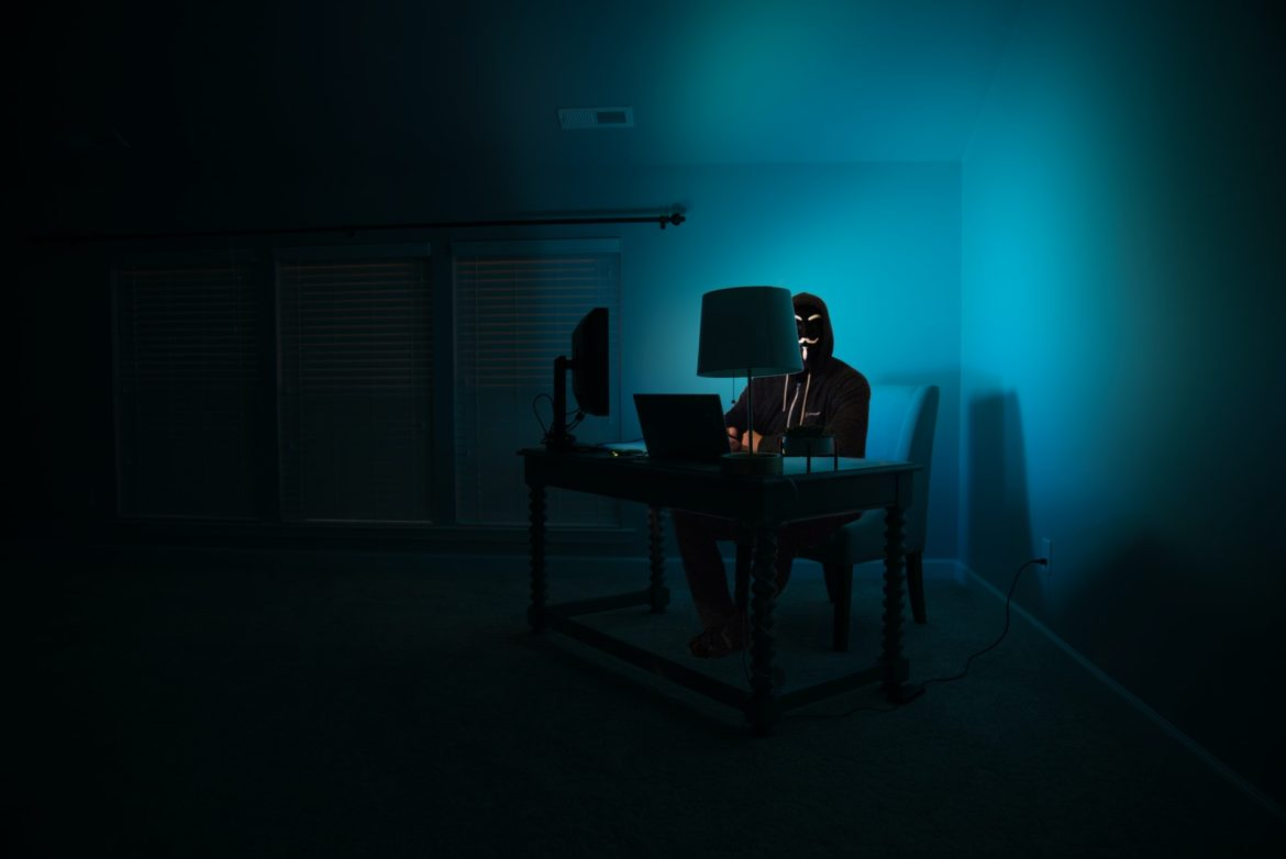 a man at a computer disguised as an anonymous hacker